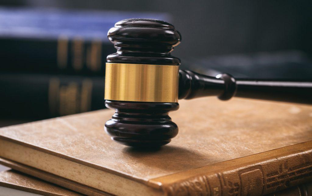 Judge gavel on law books, wooden desk
