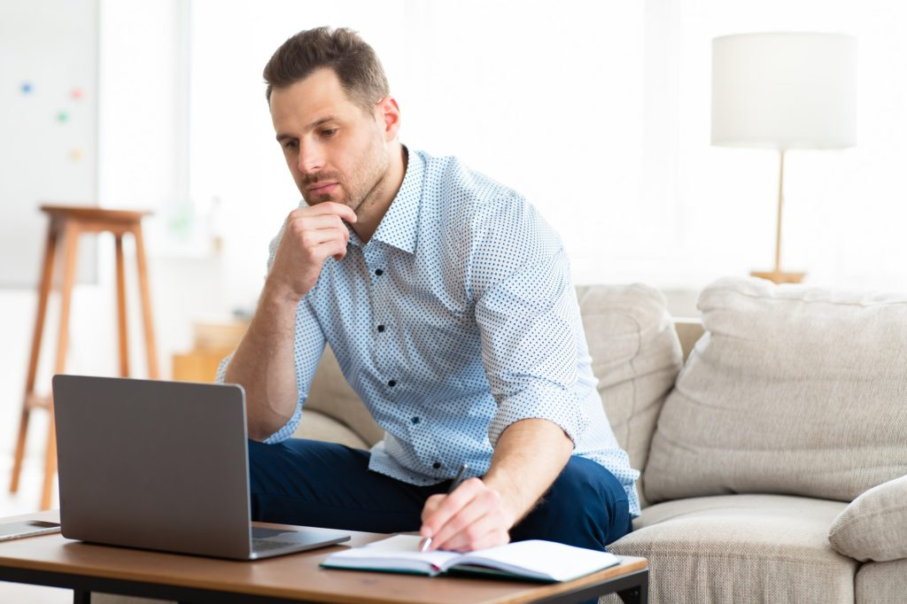 Pensive man using laptop at home and writing notes